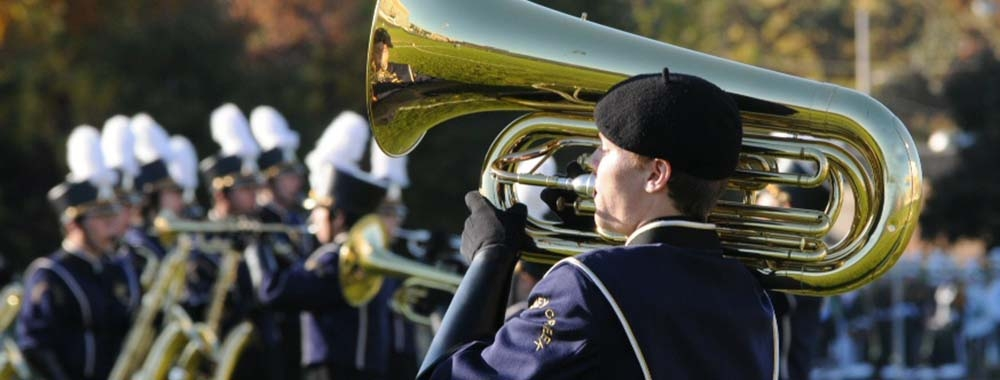 A uniformed student playing a marching tuba