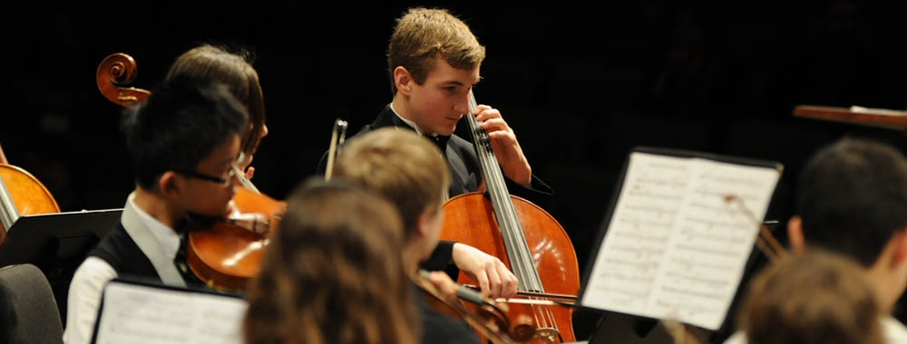 The string section of a student orchestra performing on stage